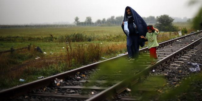 A migrant walks with his daughter at the railway track after they crossed the Serbian-Hungarian border near Roszke, southern Hungary, Friday, Sept. 11, 2015. EU officials and human rights groups say they've been disappointed by the animosity toward asylum-seekers in countries from which hundreds of thousands of people fled communist dictatorships just decades ago.(AP Photo/Matthias Schrader)